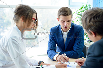 Business People Analyzing Financial Results on Graphs around the Table in Modern Office. Team Work Concept