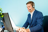 Young Customer Support Phone Operator with Headset Working in the Office.