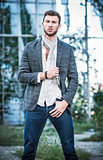 Fashion shot: portrait of handsome young man wearing jeans, shirt, jacket and scarf