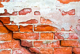 Brick wall with cracks and an old plaster as background