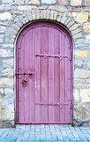 Ancient wooden door in old stone wall.