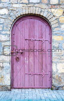 Ancient wooden door in old stone wall.