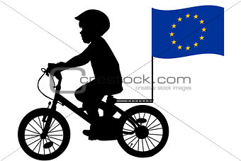 A kid rides a bicycle with European Union flag