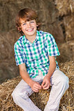 Young Happy Boy Sitting Smiling on Hay Bales