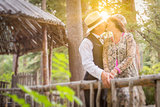 1920s Dressed Romantic Couple Kissing on Wooden Bridge