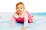 baby girl with pacifier crawling on the blue coverlet. Studio