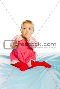 Beautiful baby sitting on a blue blanket. Studio