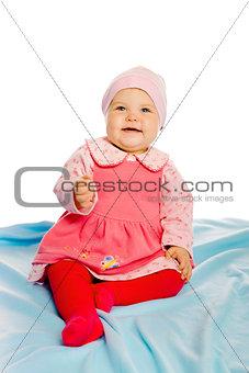 Beautiful baby sitting on a blue blanket. Studio