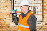 Construction worker with sledgehammer near the brick wall