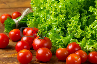tomatoes and green vegetables on wooden dark background