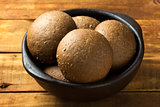 Rye bread in dark clay bowl on wooden background