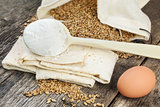 Pita bread with grains,egg and flour on old wooden table