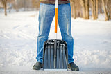 Man with a snow shovel on the trails