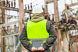 Electrician with tablet PC in electrical substation