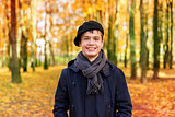 Happy teenage boy in the autumn sunny park