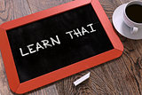 Hand Drawn Learn Thai Concept on Chalkboard.