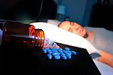pills and young man in bed