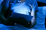 young man using a tablet in bed at night