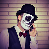 man with mexican calaveras makeup, on the phone