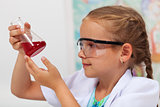 Young girl in chemistry class checking the result of an experime