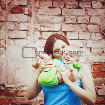 Beautiful young mother playing with baby