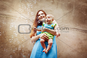 Beautiful young mother with baby blowing bubbles