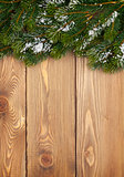Christmas fir tree with snow on rustic wooden boardc