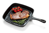 Sirloin steak with rosemary and cherry tomatoes cooking in a fry