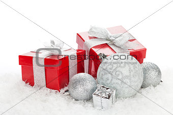 Christmas baubles and red gift boxes over snow
