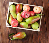 Pears and apples in wooden box on table