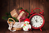 Christmas gifts and tree with alarm clock and snowman