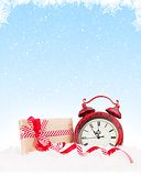 Christmas gift box and alarm clock in snow