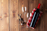 Red wine bottle, glasses and corkscrew on wooden table
