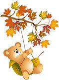 Teddy bear swinging on autumn tree branch