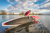 launching stand up paddleboard on lake
