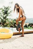 Beautiful slim girl in sexy striped bikini takes off her shorts