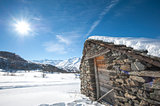 Isolated snowy mountain hut in the sun