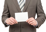 Businessman holding small blank sheet of paper