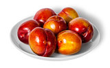 Red and yellow plums on white plate