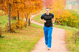 athletic man running in the park on a footpath