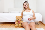 Young pregnant woman sitting on the floor with a teddy bear