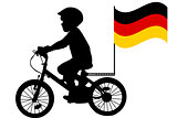 A kid rides a bicycle with German flag