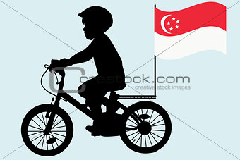 A kid  rides a bicycle with Singapore flag