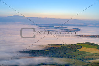 Beautiful landscape view of hills and meadows, mist and clouds