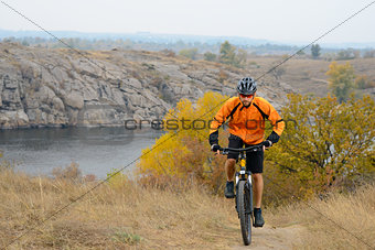 Cyclist Riding Bike on the Beautiful Autumn Mountain Trail under River