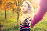 Young Woman Holding Hands on Autumn Background