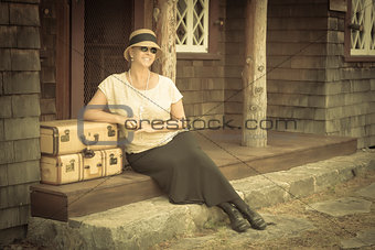 1920s Dressed Girl and Suitcases on Porch with Vintage Effect