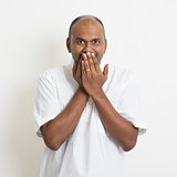 Mature casual business Indian man covered mouth