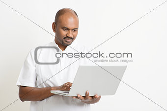 Mature Indian man using laptop