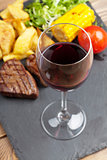 Red wine glass and steak with grilled potato, corn, salad